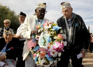 Pearl Harbor Suvivors Marvin Rewerts, 89, right, Nelson Mitchell, 91, middle, walk with a wreath to place at the USS Arizona Memorial, as fellow survivor Darnel Rogers, 91, left, looks on, at the Peal Harbor Remembrance Day ceremonies Wednesday, Dec. 7, 2011, in Phoenix. This year marks the 70th anniversary of the attack on Pearl Harbor. (AP Photo/Ross D. Franklin)